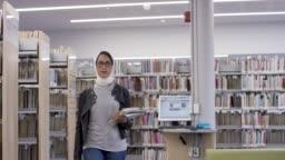 Muslim university student walking through the library