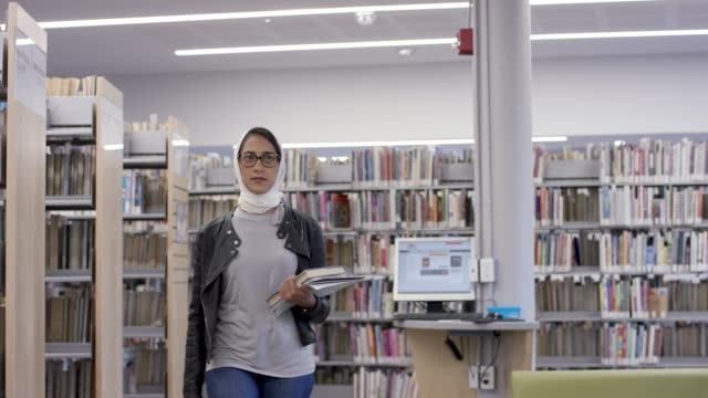 muslim university student walking through the library - person in education stock videos & royalty-free footage