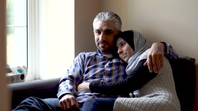 vídeos y material grabado en eventos de stock de mujer musulmana y su esposo poner juntos y riendo en su casa - pijama