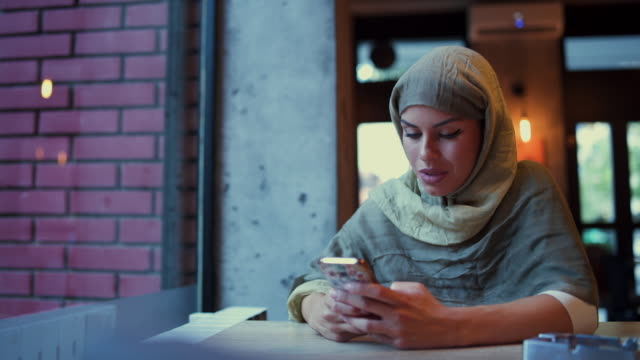 携帯電話でカフェのテキスト メッセージでイスラム教徒の女性 - モデスト・ファッション点の映像素材/bロール
