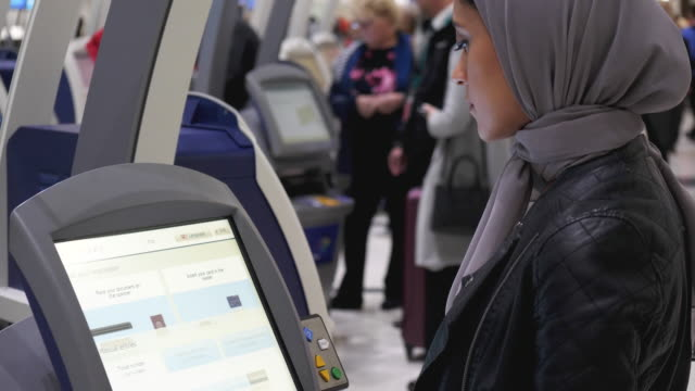 muslim woman at airport kiosk - emigration and immigration stock videos & royalty-free footage