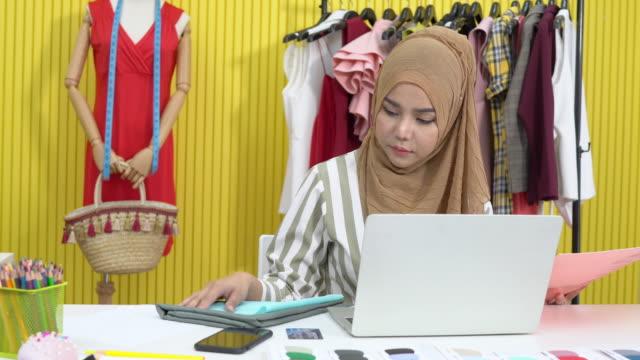 vidéos et rushes de le concepteur musulman de mode de tissu de femme travaille sur l'ordinateur portatif pour la sélection de tissu au studio à la maison - vêtement religieux