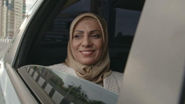 vídeos de stock, filmes e b-roll de muslim woman day dreaming in back seat - hijab