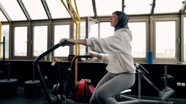 muslim woman exercising at the gym - cross trainer stock videos & royalty-free footage