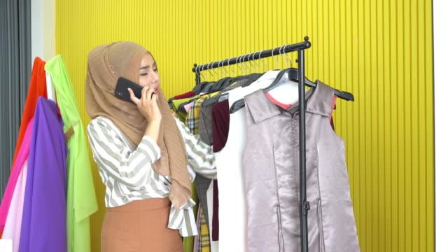 イスラム教徒の女性のファッションデザイナーは、ラック上の服を選択し、自宅のスタジオで顧客と電話を話します。 - 生地サンプル点の映像素材/bロール