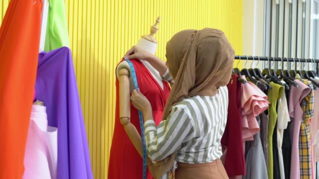 自宅のスタジオでモデルを測定するイスラム教徒の女性ファッションデザイナー。 - トルソー点の映像素材/bロール
