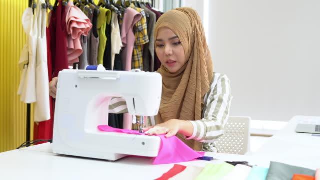 muslimische frau modedesigner textil auf elektrische nähmaschine zu hause studio, pan schuss - maßkonfektion stock-videos und b-roll-filmmaterial