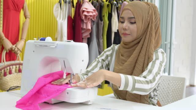 muslimische frau modedesigner textil auf elektrische nähmaschine zu hause studio, tilt shot - maßkonfektion stock-videos und b-roll-filmmaterial
