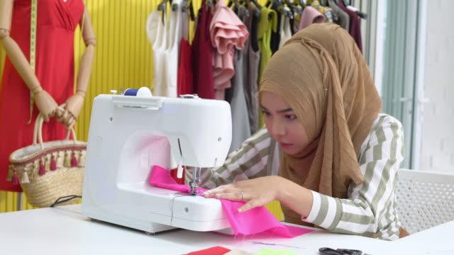 muslimische frau modedesigner textil auf elektrische nähmaschine zu hause studio - maßkonfektion stock-videos und b-roll-filmmaterial