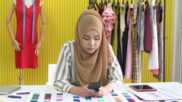 vídeos de stock, filmes e b-roll de mulher muçulmana estilista de moda digitando telefone inteligente em amostras de tecido e paleta de cores - vestimenta religiosa