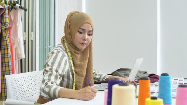 イスラム教徒の女性ファッションデザイナーは、ラップトップで働き、自宅のスタジオで描画するスケッチ - 生地サンプル点の映像素材/bロール