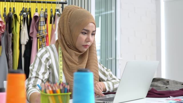 イスラム教徒の女性のファッションデザイナーは、ラップトップに取り組み、自宅のスタジオで絵を描くスケッチ、パンショット - トルソー点の映像素材/bロール