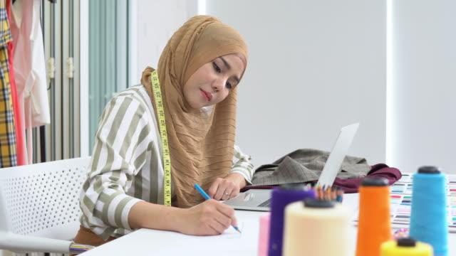 イスラム教徒の女性のファッションデザイナーは、ラップトップに取り組み、自宅のスタジオで絵を描くスケッチ、パンショット - 生地サンプル点の映像素材/bロール