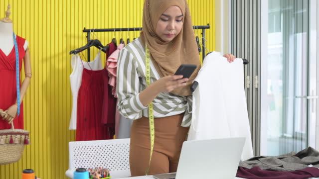 イスラム教徒の女性のファッションデザイナーは、自宅のスタジオで顧客とラップトップと話し電話で働きます - トルソー点の映像素材/bロール