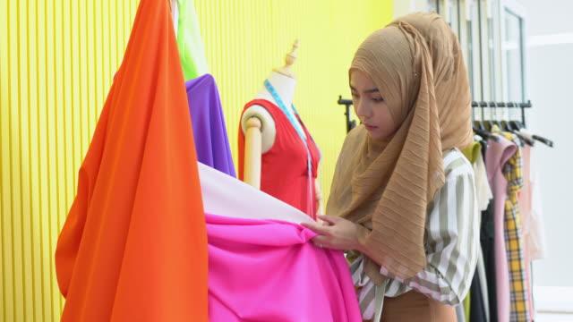 生地とカラーパレットに取り組むイスラム教徒の女性ファッションデザイナー - 生地サンプル点の映像素材/bロール