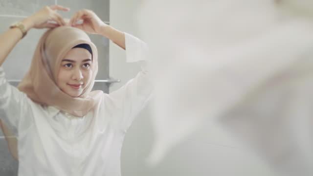 stockvideo's en b-roll-footage met moslim vrouw aankleden en kijken naar spiegel thuis. - paskamer