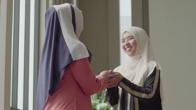 muslim woman greeting her friend and talking with smile - islam stock videos & royalty-free footage