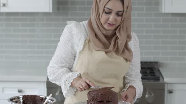 vidéos et rushes de gâteau de chocolat de glaçage de femme musulmane - vêtement religieux