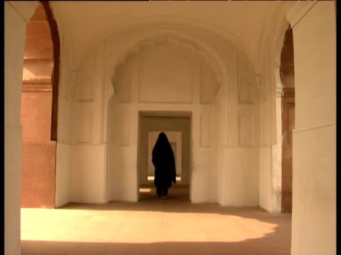 vídeos de stock, filmes e b-roll de a muslim woman in black hijab walks down cloister in mosque - vestimenta religiosa