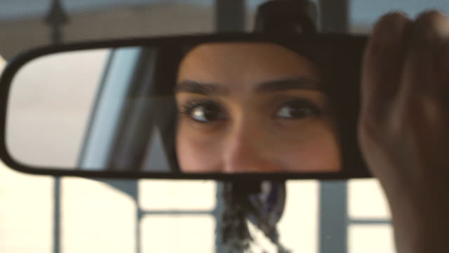 muslim woman in hijab correcting car rear-view mirror - rear view mirror stock videos & royalty-free footage