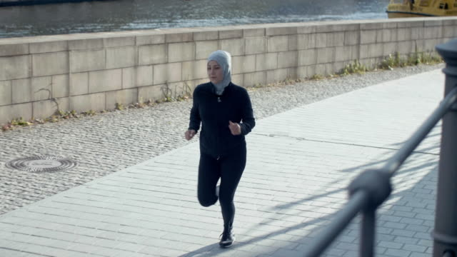 muslim woman in sport hijab running near canal (slow motion) - hijab stock videos and b-roll footage