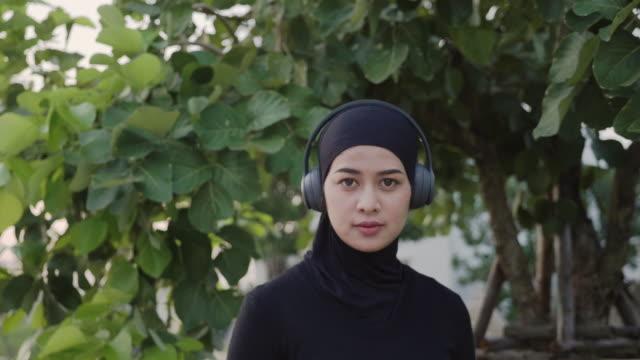 muslimsk kvinna jogging med sina hörlurar i parken, koncept övning, - trådlös teknologi bildbanksvideor och videomaterial från bakom kulisserna