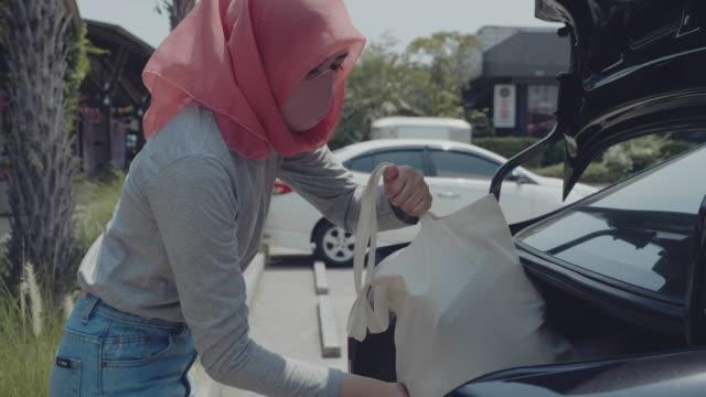 vídeos de stock e filmes b-roll de muslim woman load grocery bags in back of the car - saco objeto manufaturado