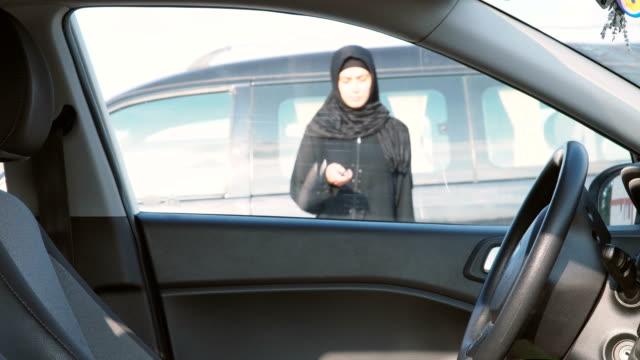 donna musulmana che apre le porte dell'auto - remote control video stock e b–roll