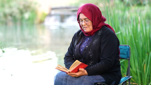 muslim woman reading a book at park - senior women stock videos & royalty-free footage