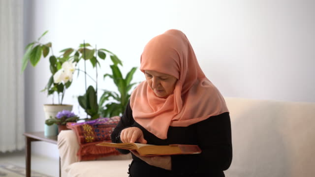 muslim woman reads quran at home in ramadan, turkey - headscarf stock videos & royalty-free footage