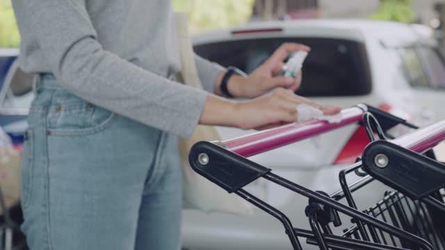 stockvideo's en b-roll-footage met moslimvrouw die boodschappenwagenhandvat met antibacteriële nevel ontsmet - vermijden