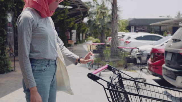 muslim woman sanitizing shopping cart handle with antibacterial spray - rubbing alcohol stock videos & royalty-free footage