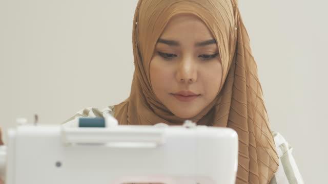 vídeos de stock e filmes b-roll de cu: muslim woman sewing garment - estilista de moda designer profissional