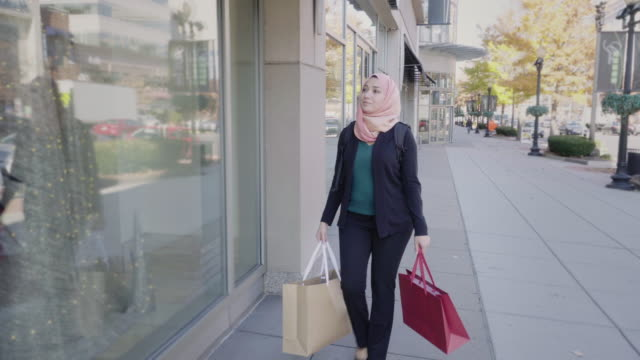 muslim woman shopping in urban setting - hijab stock videos and b-roll footage