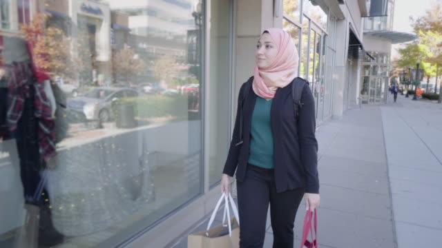 vídeos de stock, filmes e b-roll de mulher muçulmana, compras em ambiente urbano - vestuário modesto