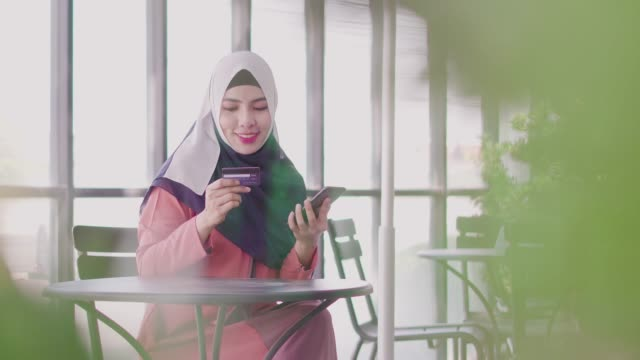 muslim woman shopping online with credit card and smartphone. - hijab stock videos & royalty-free footage
