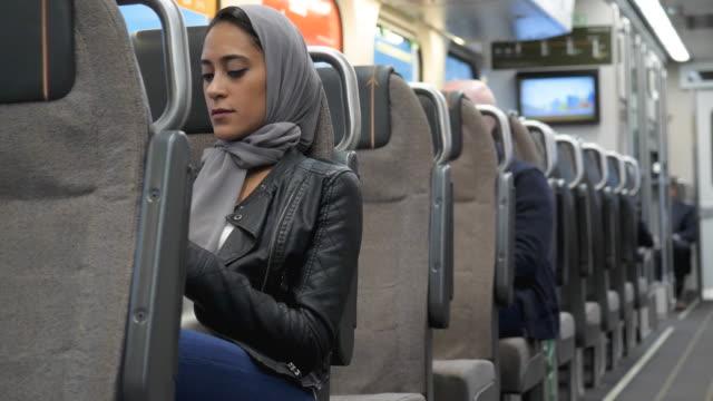 vídeos de stock, filmes e b-roll de mulher muçulmana que senta-se no trem - passenger