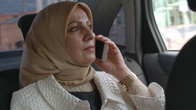 muslim woman talking on phone in car - mid adult stock videos & royalty-free footage