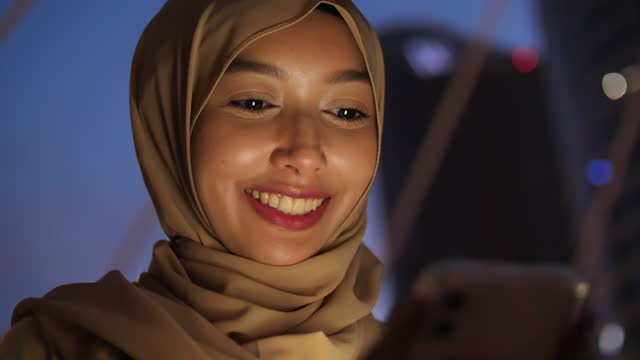muslim woman texting massage on mobile devices at night - islam stock videos & royalty-free footage