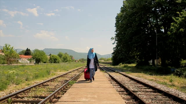 vídeos de stock, filmes e b-roll de viajante da mulher muçulmana na estação ferroviária - vestuário modesto