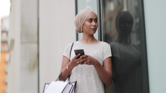 muslim woman using a smartphone on a shopping trip - window display stock videos & royalty-free footage