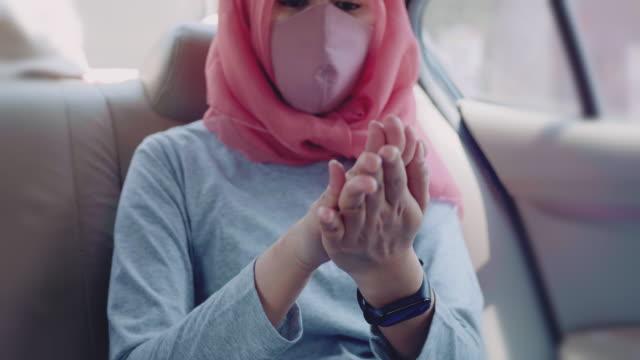 vidéos et rushes de femme musulmane utilisant le désinfectant de main tout en s'asseyant dans la voiture - passager