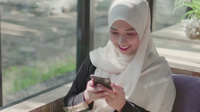 muslim woman using smartphone for social media. - hijab stock videos & royalty-free footage