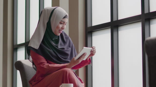 イスラム教徒の女性は、コーヒー ショップでタブレットを使用しています。 - モロッコ文化点の映像素材/bロール