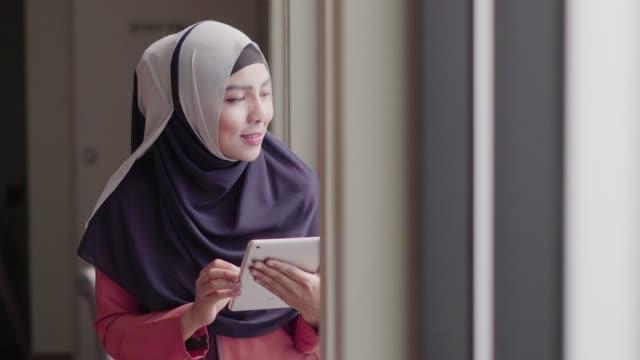 muslimische frau mit tablet im kaffeehaus - kultur des nahen osten stock-videos und b-roll-filmmaterial