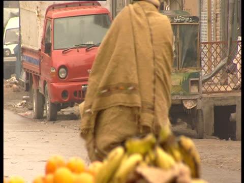 muslim woman walking along street - religiöse kleidung stock-videos und b-roll-filmmaterial