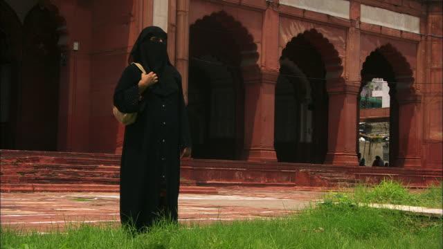 a muslim woman wears a hijab as she stands near the jama masjid mosque. available in hd. - 僧衣点の映像素材/bロール
