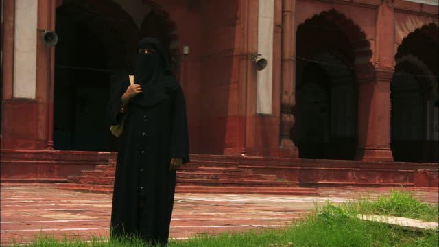 a muslim woman wears a traditional hijab as she stands near the jama masjid mosque. available in hd. - 僧衣点の映像素材/bロール