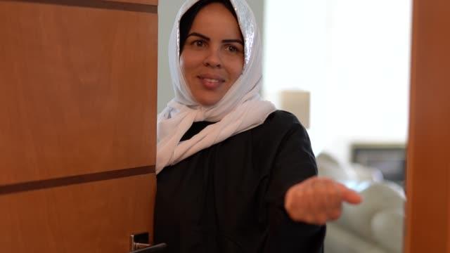muslim woman welcoming people open her door - woman doorway stock videos & royalty-free footage