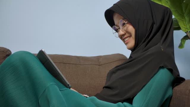笑顔のイスラム教徒の女性、映画を見て自宅のリビングルームのソファに座って、コロナウイルス検疫期間中に彼女のタブレット携帯電話からシリーズ - モデスト・ファッション点の映像素材/bロール